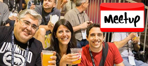 People holding drinks and smiling with Meetup logo on top