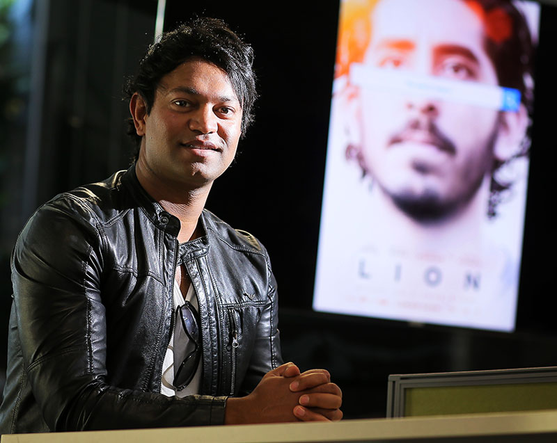 Saroo Brierley - Texas GIS Forum Keynote, speaking in front of map, picture of his book on right