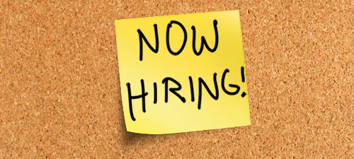 A sticky note with handwritten Now Hiring!
