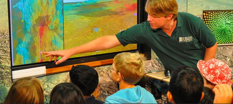 A USGS staff member shows kids a map